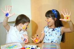 Blije kinderen met verven op hun gezichten De gezichten van kinderenverven met kleuren Stock Fotografie