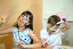 Blije kinderen met verven op hun gezichten De gezichten van kinderenverven met kleuren Stock Afbeeldingen