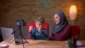 Blije kleine jongen en zijn moslimmoeder in de video van de hijabopname als vloggers op camera stock footage