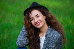 Blije, krullend-haired vrouw in een hoed Royalty-vrije Stock Foto