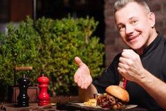 Blije mens die hamburger en Frieten in restaurant eten stock foto's