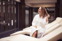 Blije midden oude vrouw in badjas het ontspannen bij kuuroordzitkamer stock afbeelding