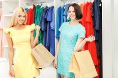 Blije modieuze meisjes die in winkel kopen stock foto