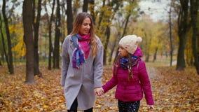 Blije moeder en dochter die van vrije tijd in de herfst genieten stock footage
