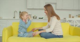 Blije moeder en dochter die van vrije tijd op bank genieten stock video