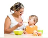Blije moederlepel die haar babymeisje voedt royalty-vrije stock afbeeldingen