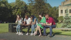 Blije multi etnische studenten die op parkbank samenkomen stock videobeelden