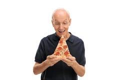 Blije oudste die een beet van pizza neemt stock afbeelding