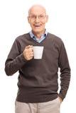 Blije oudste die een witte koffiekop houden stock afbeelding