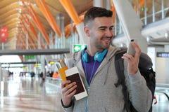 Blije reiziger die smartphone in de luchthaven gebruiken Stock Afbeeldingen