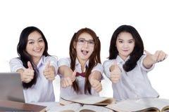 Blije studenten die handengebaar tonen stock foto's