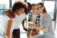 Blije studenten die slimme telefoon met behulp van royalty-vrije stock foto's