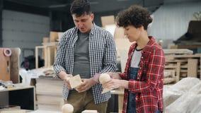 Blije timmerlieden die hout met schuurpapier oppoetsen die en in workshop spreken lachen stock videobeelden