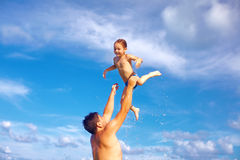 Blije vader en zoon die pret in water op tropisch strand hebben Stock Foto