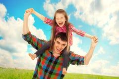 Blije vader met dochter op schouders stock afbeeldingen