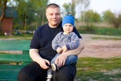 Blije vaderzitting met zijn ontstemde zoon op een bank in het park stock foto