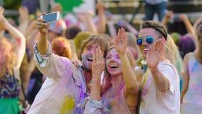 Blije vrienden die handen en dansen golven, die voor telefooncamera bij festival stellen stock videobeelden