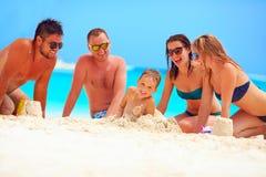 Blije vrienden die pret samen op zandig strand, de zomervakantie hebben Stock Foto's