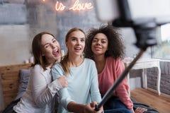 Blije vrolijke meisjes die selfie thuis nemen stock afbeeldingen