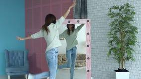 Blije vrouw die haar lichaamsvorm in spiegel controleren stock videobeelden