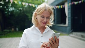 Blije vrouw die smartphone gebruiken die het scherm glimlachen bekijken die zich in openlucht bevinden stock footage