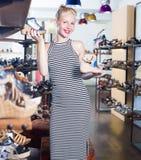 Blije vrouw die twee paren schoenen kiezen Royalty-vrije Stock Foto's