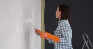 Blije vrouw het schilderen muur van nieuwe flat met een rol stock video
