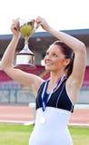 Blije vrouwelijke atleet die een trofee en een medaille houdt royalty-vrije stock fotografie