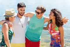 Blije vrouwen en kerels die van hun rust op strand genieten Stock Foto's
