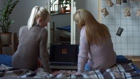 Blije vrouwen met laptop online winkelen thuis stock footage