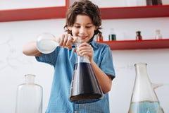 Blije weggegaane jongen die chemische vloeistoffen mengen Stock Afbeelding
