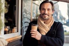 Blije zakenman die op middelbare leeftijd latte op straat drinken stock fotografie
