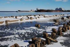 Blijft van een houten pijler en schepen in haven Stock Afbeeldingen