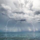Bliksem en onweersbui boven overzees Stock Foto's