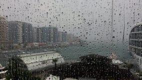 Blikseminslag door regendalingen wordt gezien op het venster dat
