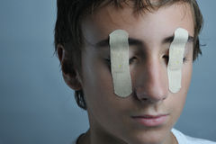 Blind. Portrait of a boy with bandaids over his eyes stock photography