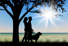 Blind couple with cane and dog guide under tree near sea day Royalty Free Stock Image