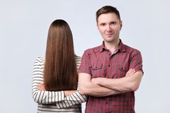 Blind day concept. Young couple standing at studio. Man is smiling, Girl is hiding her face with hair feeling shy royalty free stock photography