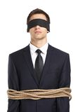 Blind-folded businessman tied with the line Royalty Free Stock Image