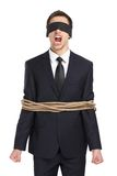 Blind-folded businessman tied with the rope screams Stock Image