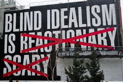 Blind Idealism is art exhibit. Artist Barbara Kruger's untitled creation as it's placed on the side of a building at high line park New York City by two workers Stock Photo