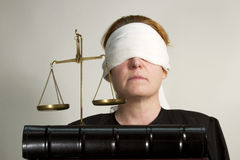 Blind Justice. Woman dressed in legal robes wearing a blindfold with legal scales and books Royalty Free Stock Photo