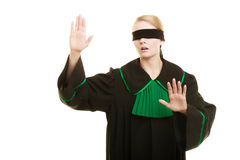 Blind justice. Woman covering eyes with blindfold. Blind justice. Woman lawyer attorney wearing classic polish (Poland) black green gown covering eyes with Royalty Free Stock Image