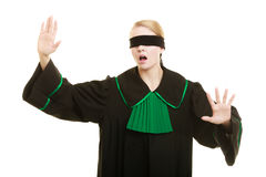 Blind justice. Woman covering eyes with blindfold. Blind justice. Woman lawyer attorney wearing classic polish (Poland) black green gown covering eyes with Stock Photography