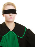 Blind justice. Woman covering eyes with blindfold. Blind justice. Woman lawyer attorney wearing classic polish (Poland) black green gown covering eyes with Royalty Free Stock Images