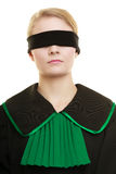 Blind justice. Woman covering eyes with blindfold. Blind justice. Woman lawyer attorney wearing classic polish (Poland) black green gown covering eyes with Stock Image