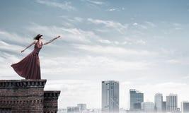 Blind kvinna i lång röd klänning överst av byggnad Blandat massmedia arkivfoto