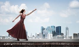 Blind kvinna i lång röd klänning överst av byggnad Blandat massmedia arkivbilder