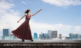 Blind kvinna i lång röd klänning överst av byggnad Blandat massmedia royaltyfri fotografi