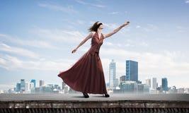 Blind kvinna i lång röd klänning överst av byggnad Blandat massmedia royaltyfri bild